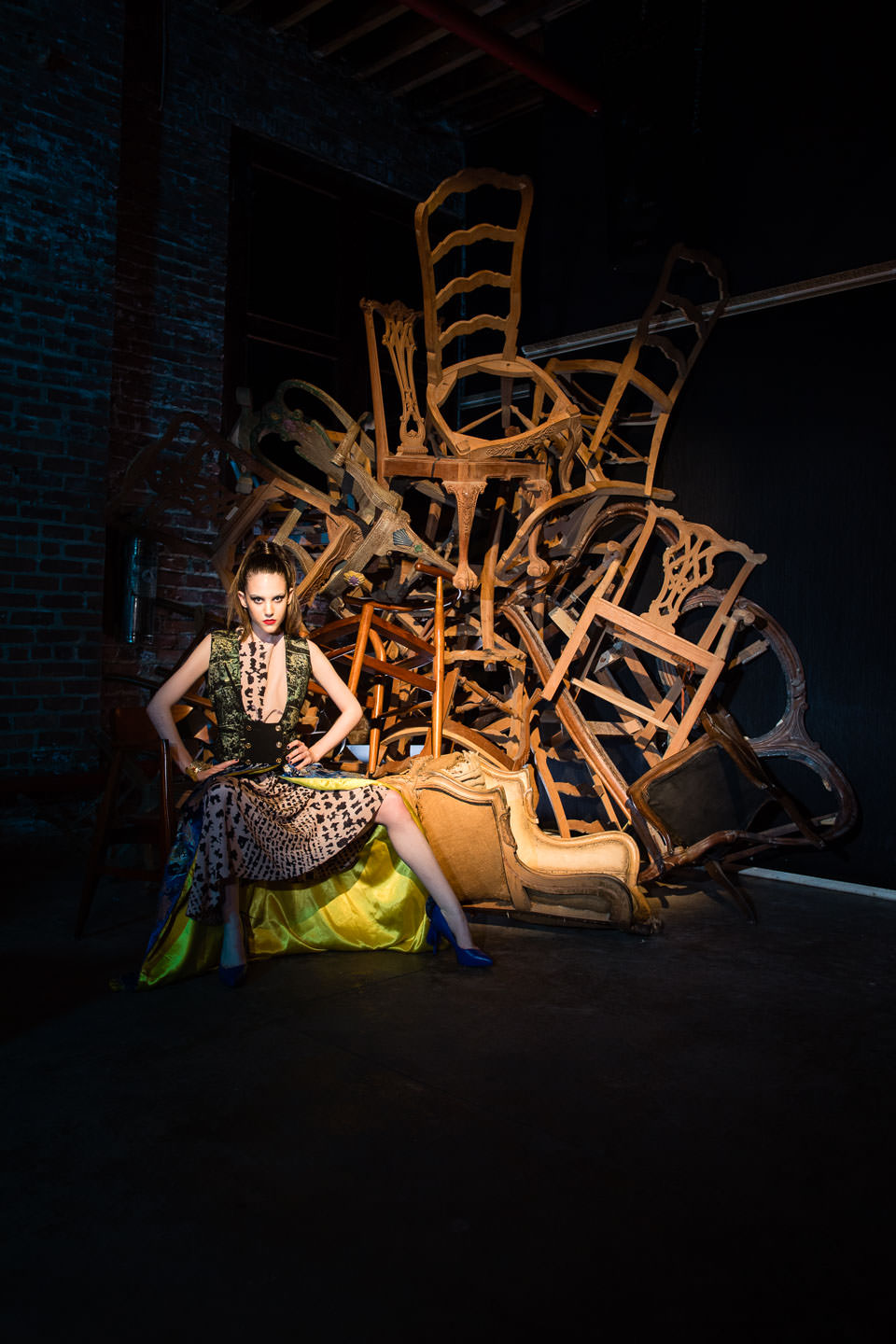 model sitting next to creative stack of chairs at monaliza studios in brooklyn ny editorial night