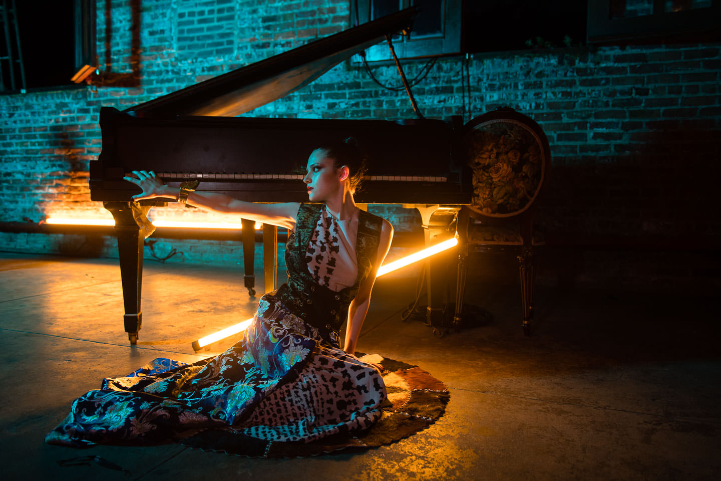 model sitting under piano with orange neon lights at monaliza editorial night