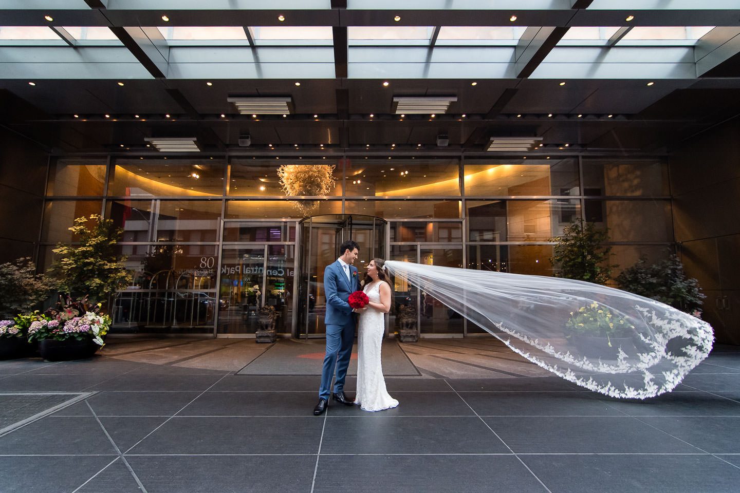 bride and groom in front of mandarin oriental hotel in nyc with her veil flying in the wind