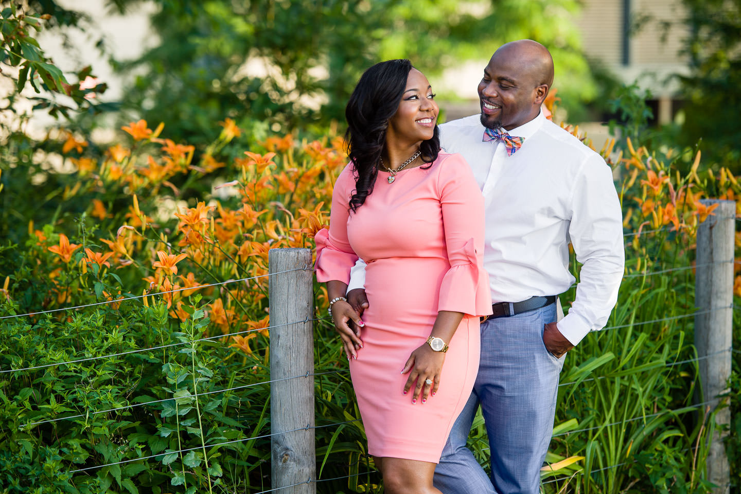 black couple engagement session in dumbo during spring in front of flowers and bushes