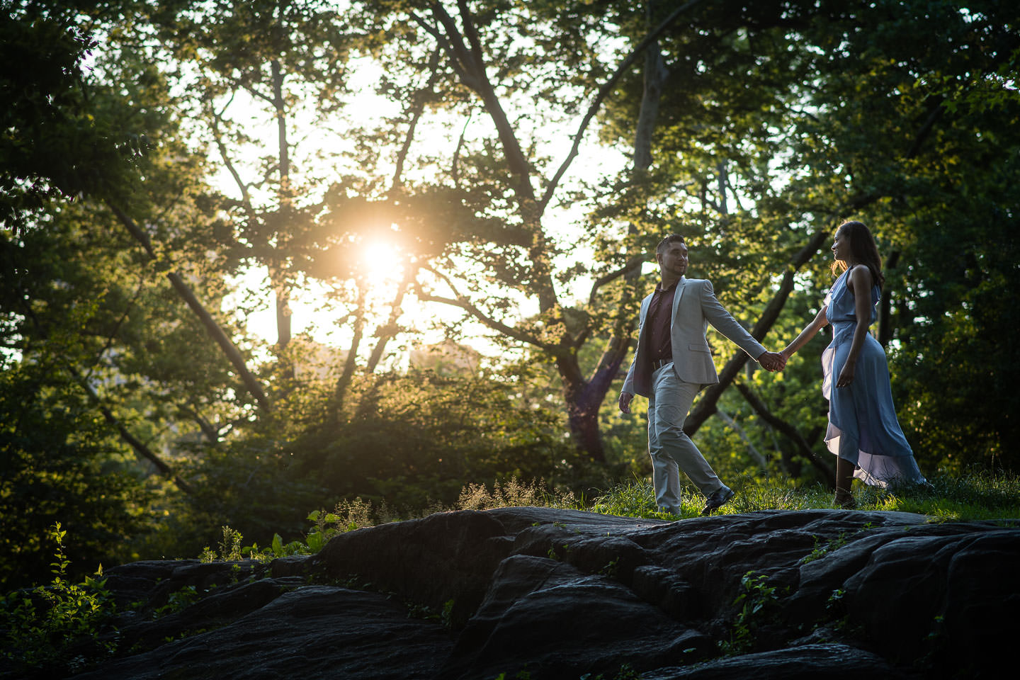 central park engagement session at sunset walking on rocks holding hands