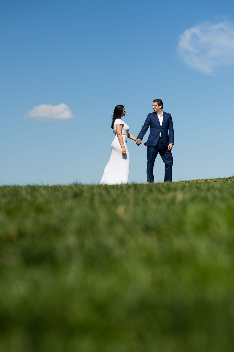couple holding hands on grassy hill against blue sky in formal outfits