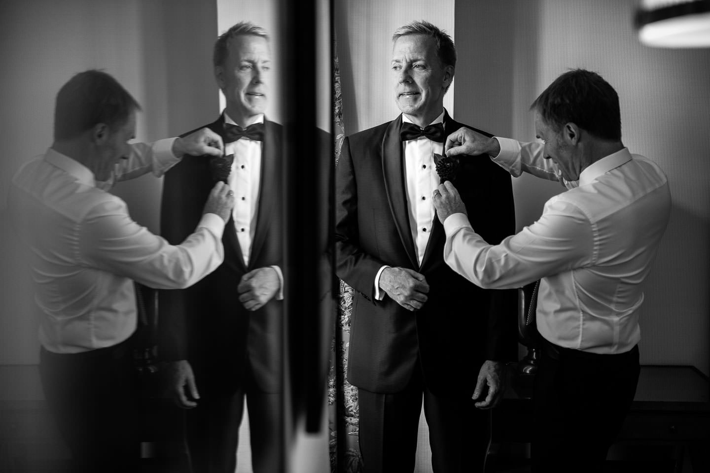 groom getting ready at the yale club with his best man helping