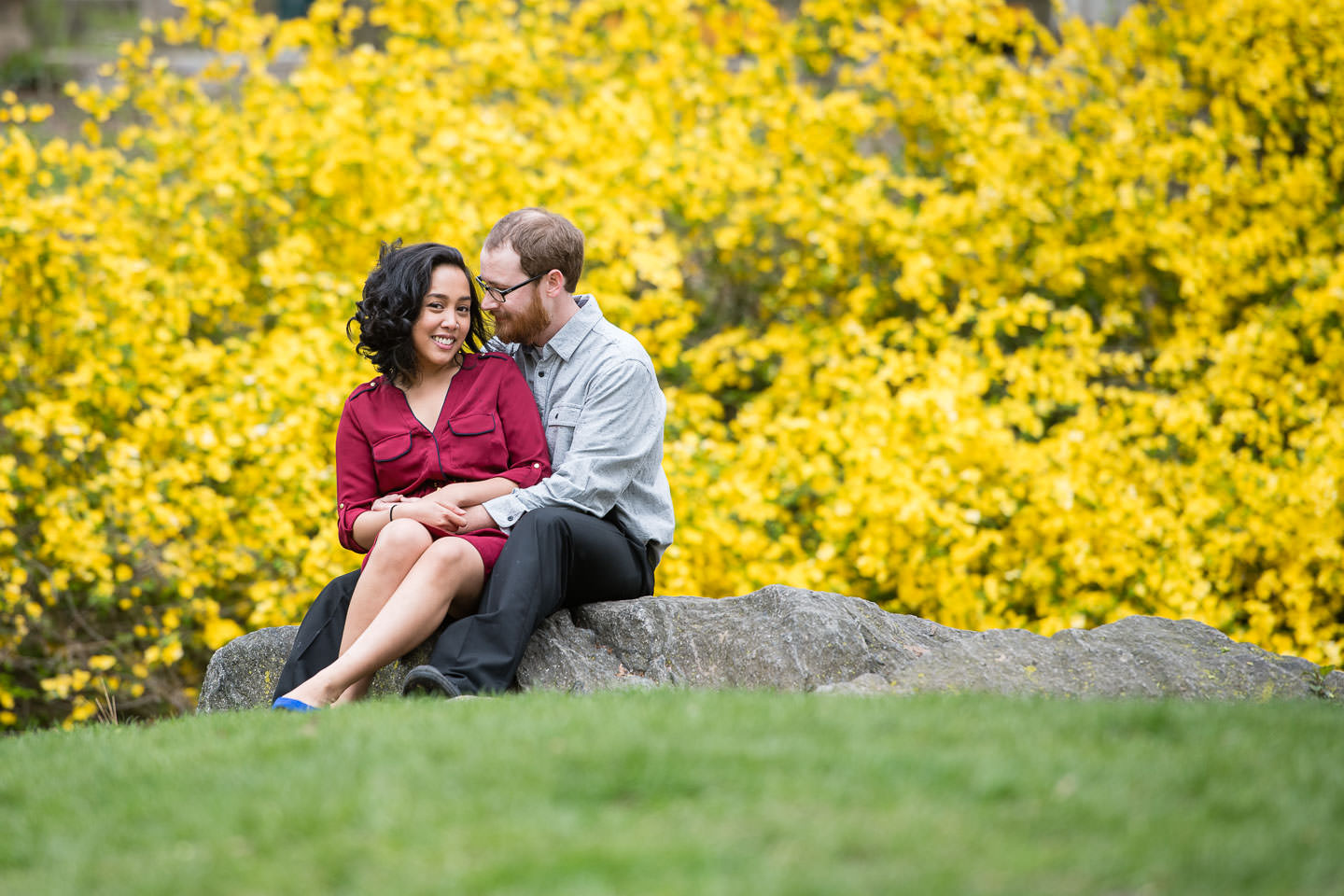 nyc spring engagement session of couple sitting on rock with yellow flowers behind them
