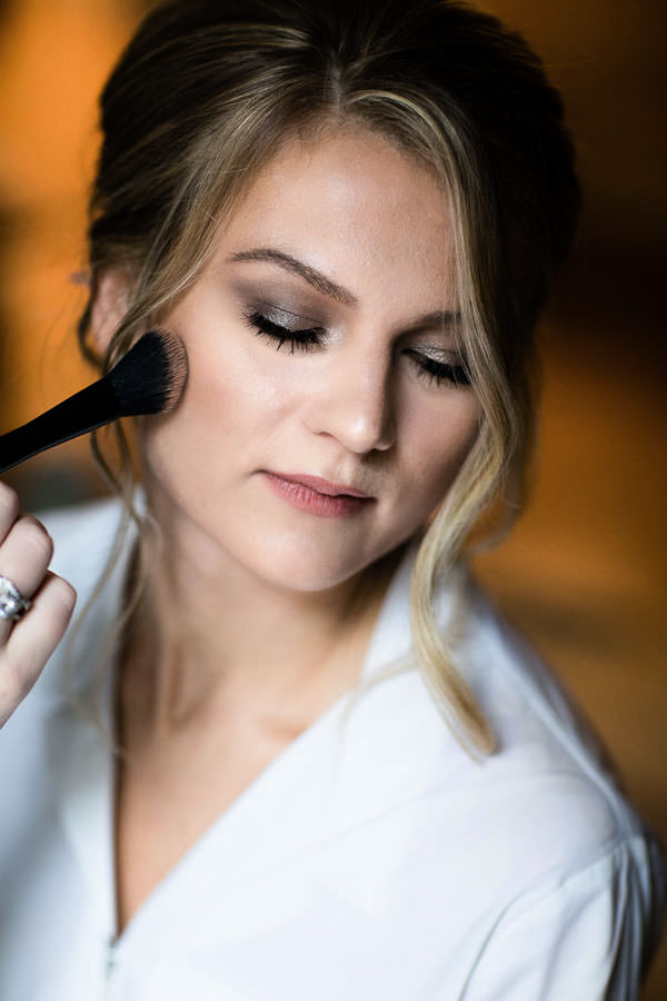 beautiful bride applying makeup on for her wedding day