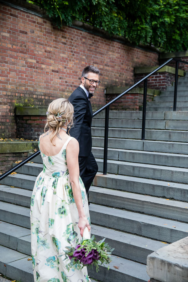 bride and groom walking up stairs in central park conservatory garden by pergola