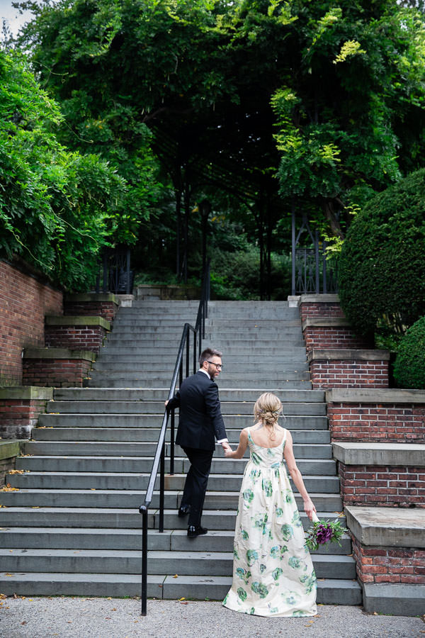 bride and groom walking up stairs of the Conservatory gardens in NYC