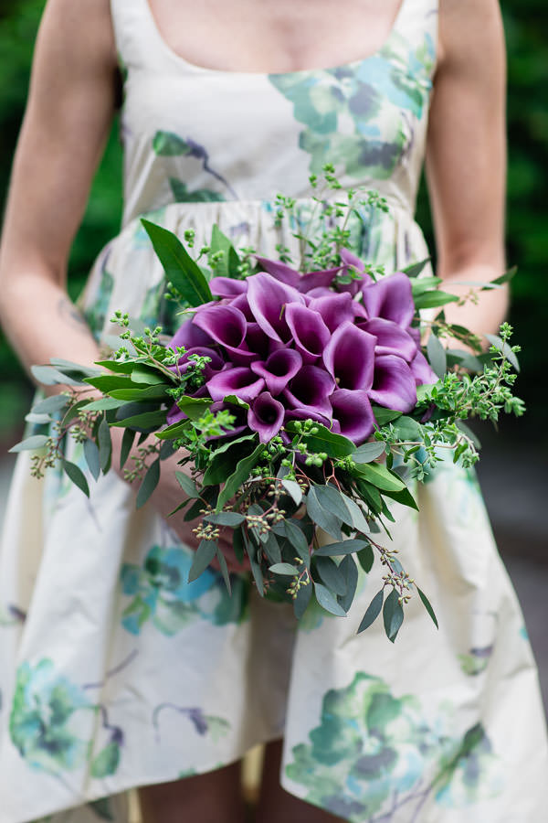 bride holding purple bridal bouquet in hands with wedding dress on for wedding photoshoot in new york city
