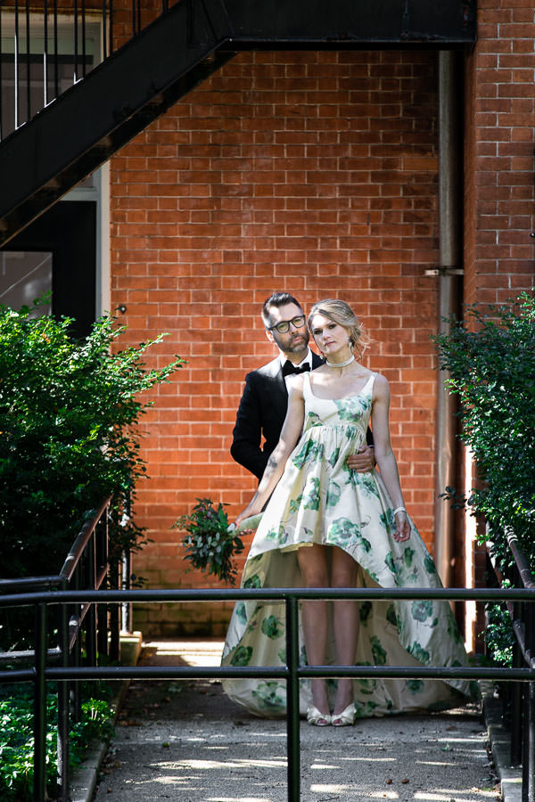 groom in tuxedo holding bride wearing a wedding dress in front brick wall