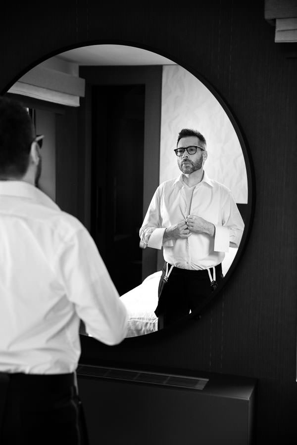 groom putting his dress shirt on for his wedding day while looking in the mirror