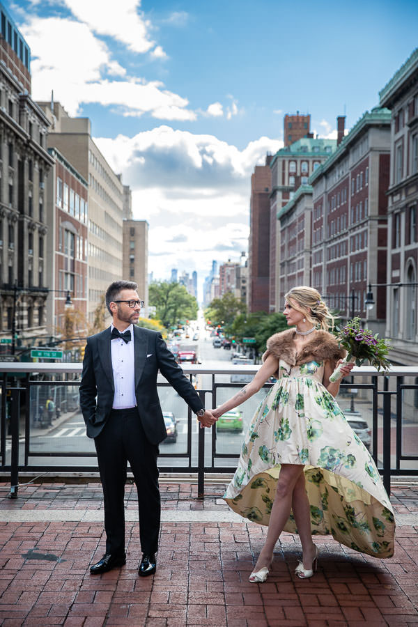 Bride and Groom holding hands with new york city scenery in the background
