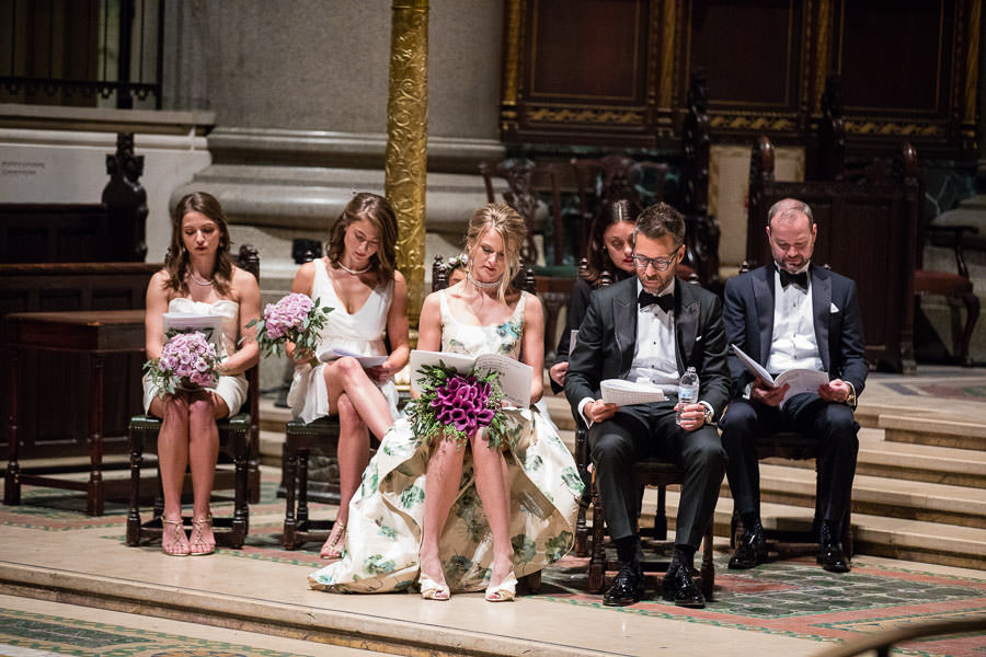 bride and groom sitting reading church scripture on the alter with bridesmaids and groomsmen
