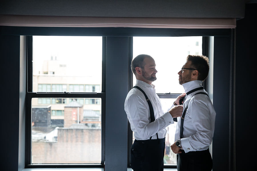 groomsman helping groom tie his tie at the Time New York Hotel in NYC