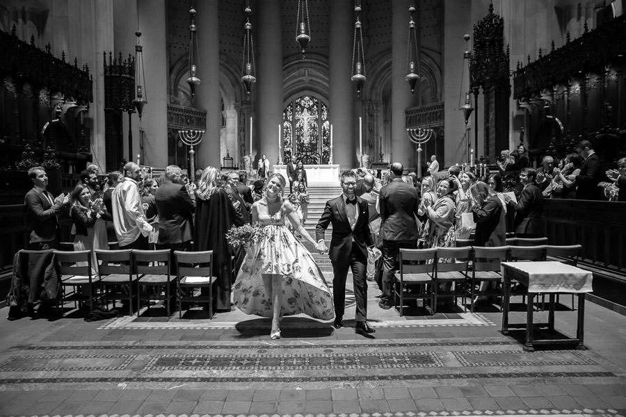 black and white photo of bride and groom on their wedding day leaving the church