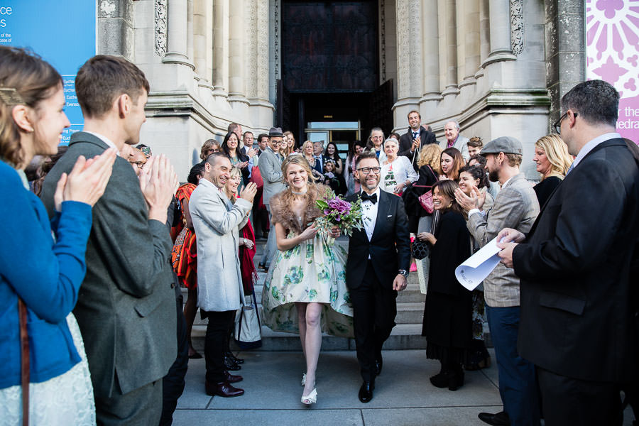 newlyweds leaving The Cathedral of Saint John the Divine on their wedding day in new york city