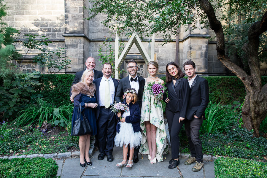 newlywed couple posing with family and flower girl in the gardens of The Cathedral of Saint John the Divine