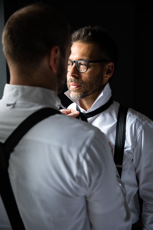 groomsman helping groom get ready for his wedding day