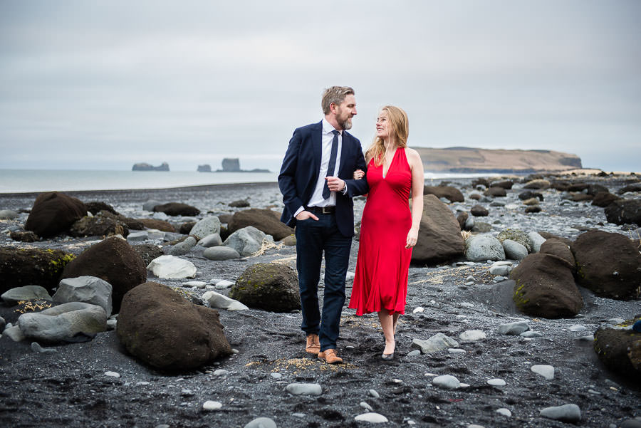 engaged couple walking on black beach in Vik, Iceland for their destination engagement session
