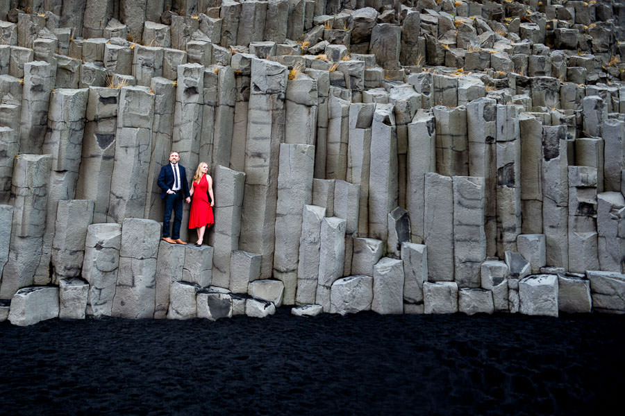 engaged couple standing on rocks at vik beach in Iceland for their destination engagement session