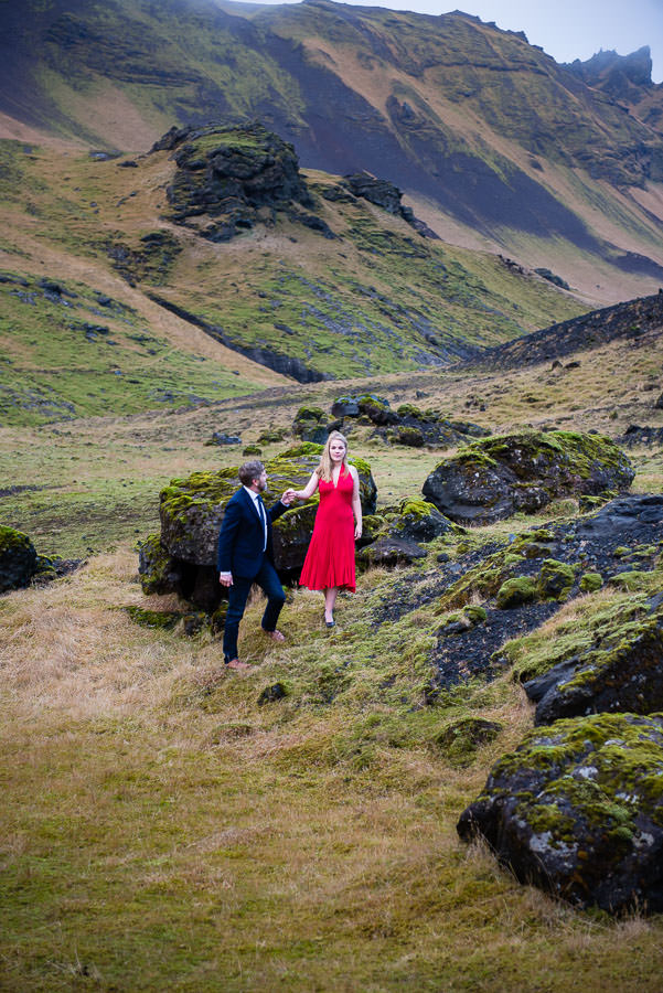 couple poses on green mountain top in Iceland for their destination engagement session