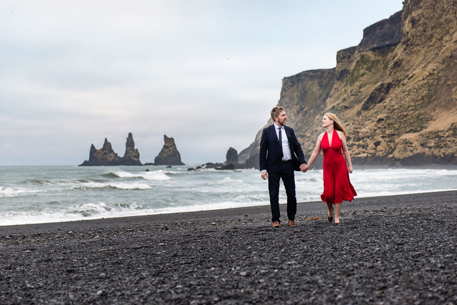 couple walks on the beach in iceland for their destination engagement session