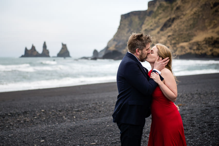 couple kisses in front of ocean in vik, iceland for their destination engagement session