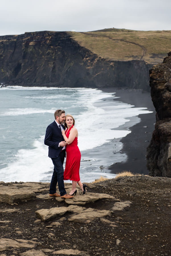 engaged couple in iceland pose at Vik beach in iceland