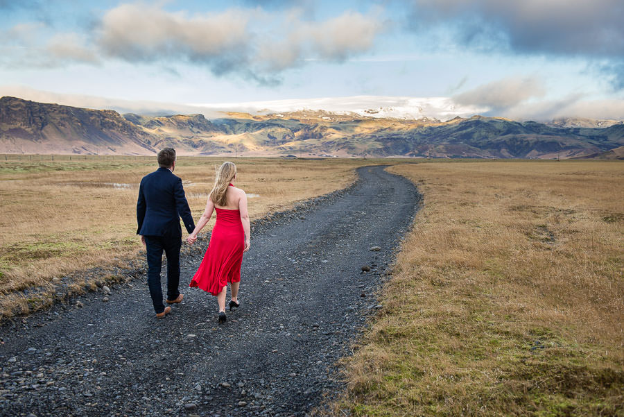 husband and wife walk on road in iceland with mountains in the background and she is wearing a red evening gown
