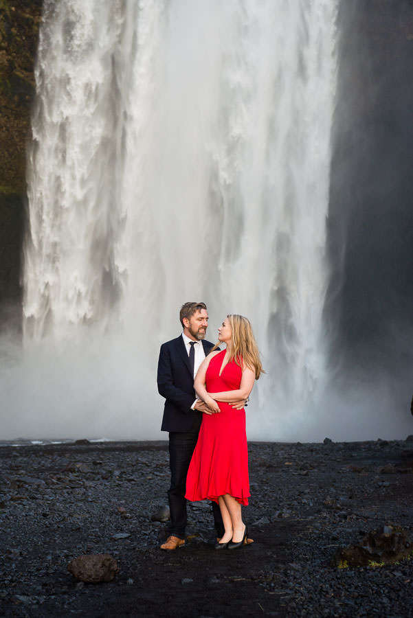 girl in red dress in front of skogafoss waterfall in iceland with her husband for destination engagement session