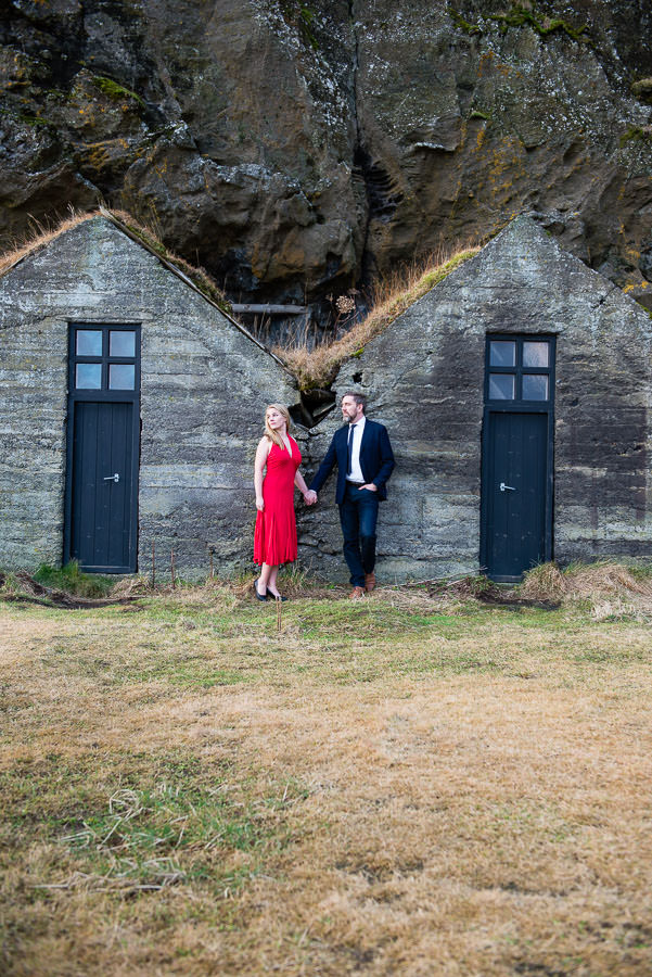 couple in iceland poses by turf houses