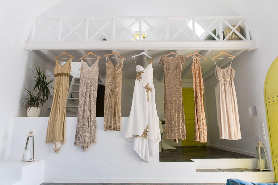bridesmaid dresses and bridal gown hanging from balcony in santorini greece for destination wedding