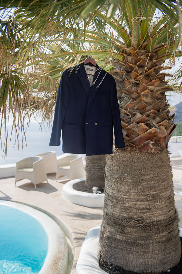 hockerty suit jacket hanging from palm tree in santorini