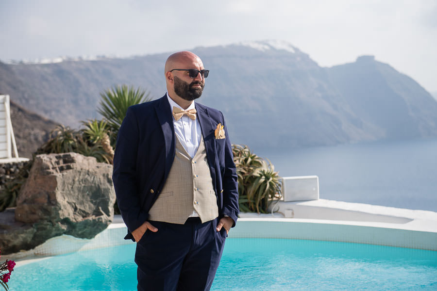 groom standing by exotic pool in santorini for destination wedding photography