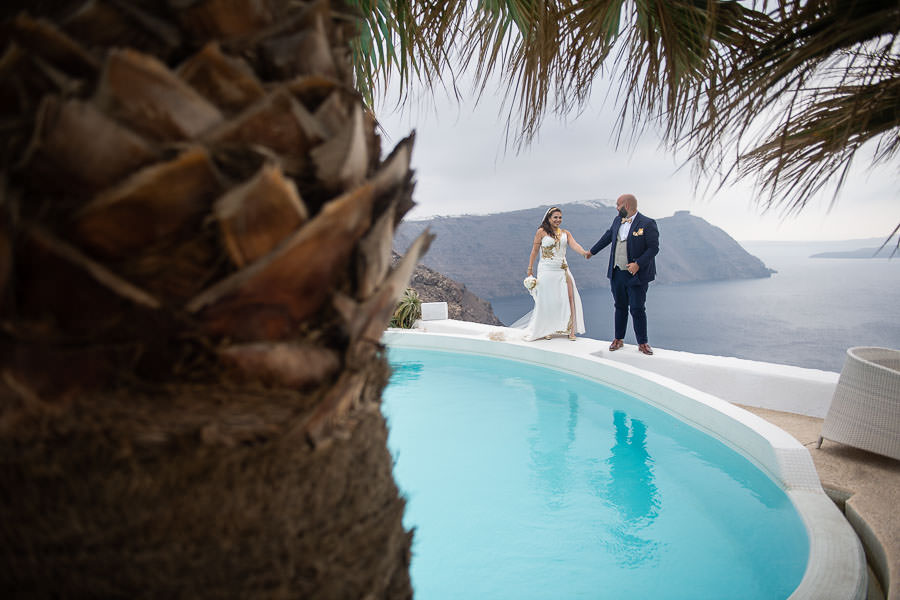 bride and groom pose by pool at diamond rock villa