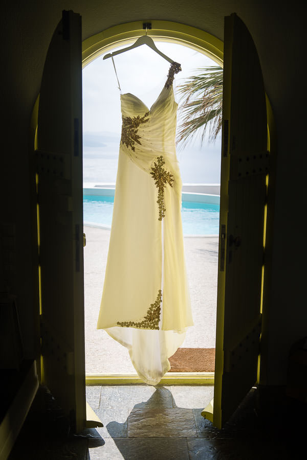 white and gold wedding gown hanging in exotic destination wedding at santorini