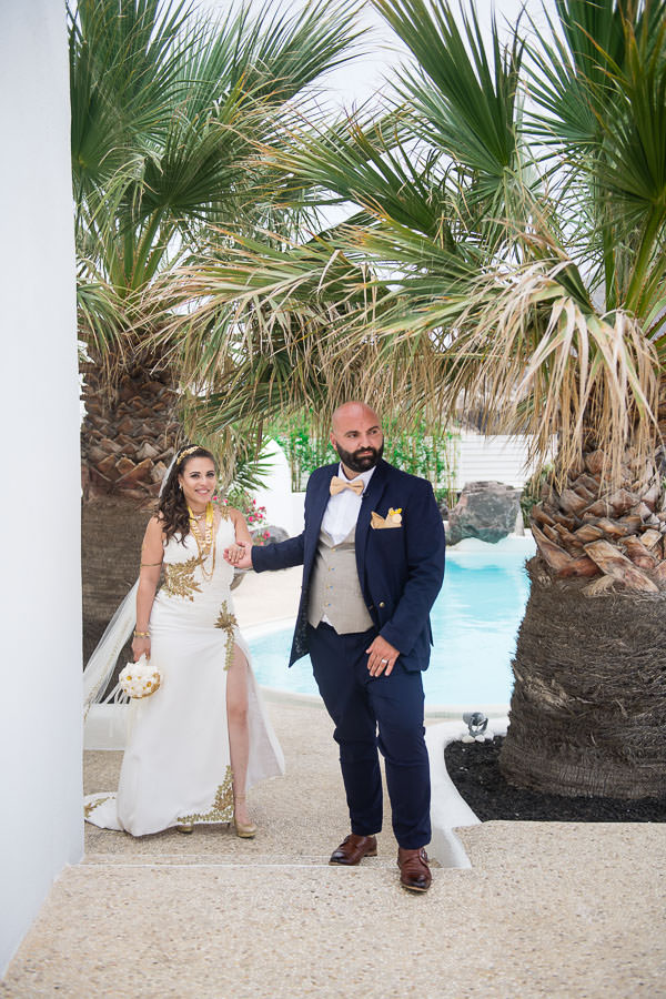 bride and groom walk next to palm tree in diamond rock villa in santorini