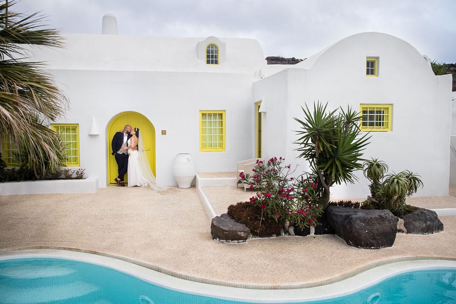 bride and groom pose by door at their villa in santorini