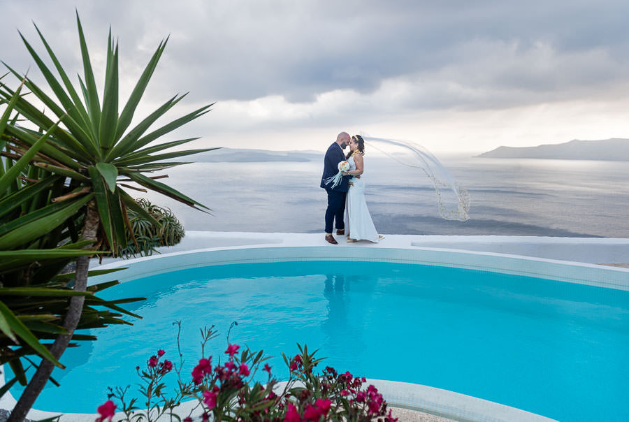 bride and groom by pool at villa in santorini for their destination wedding with palm tree and veil flying in the wind