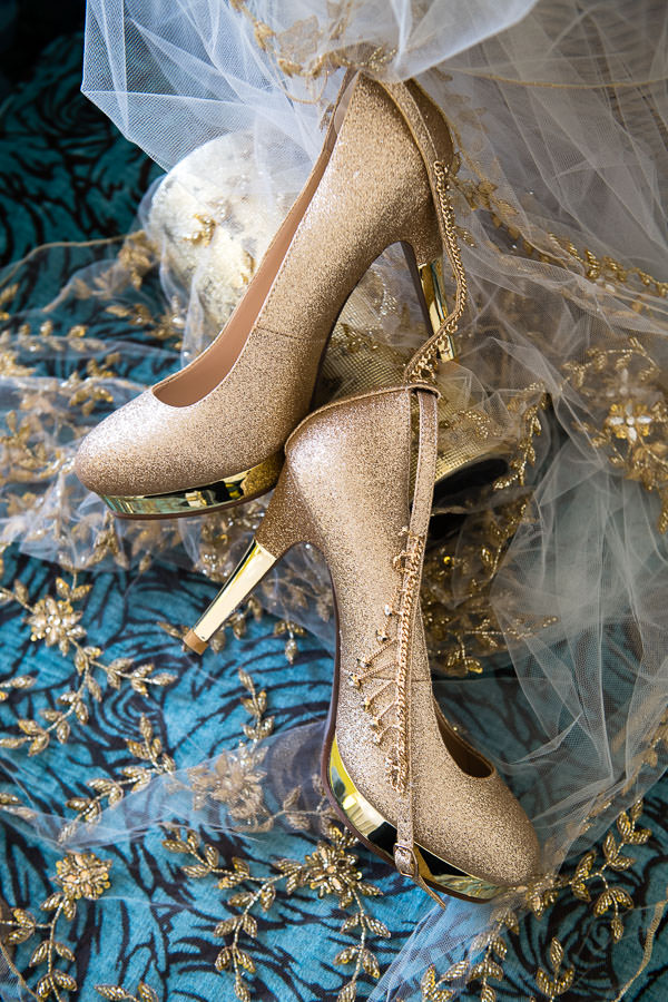 detail shot of gold wedding heels by window in santorini