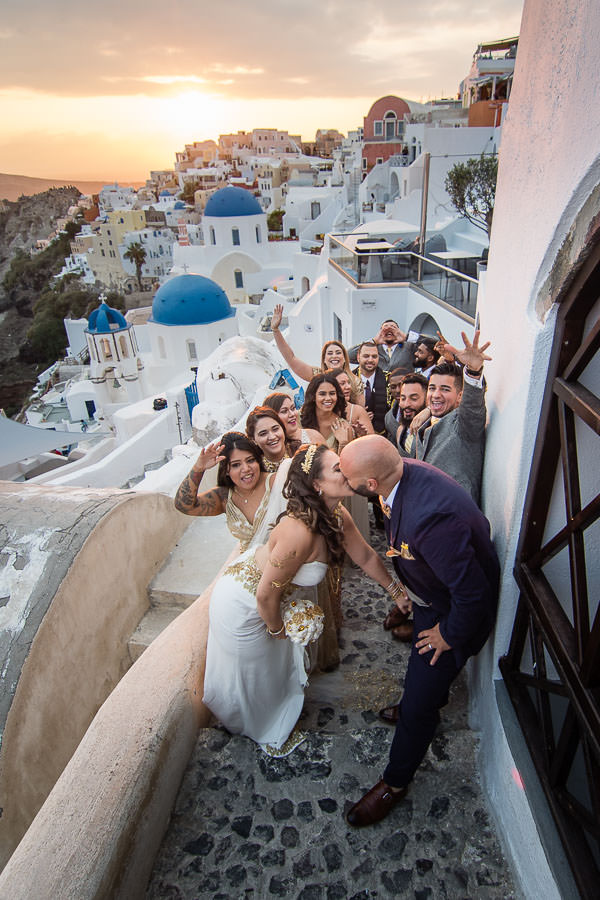 bride and groom with bridal party at sunset at city of oia santorini greece for a destination wedding