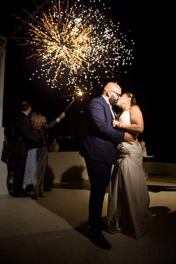 bride and groom kiss under fireworks in diamond rock villa santorini
