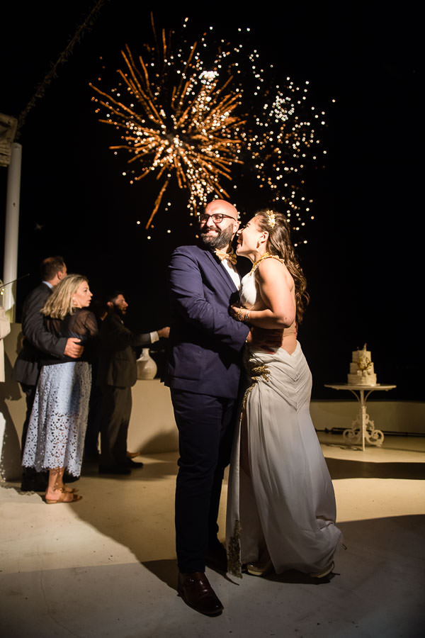 couple kisses under fireworks show at their destination wedding in santorini, greece