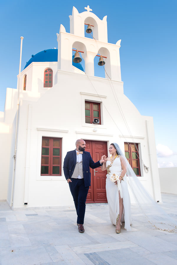 bride and groom walks in front of white church at their destination wedding in santorini, greece