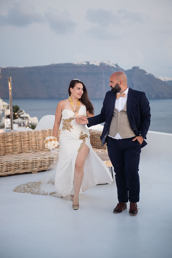 bride and groom walks on rooftop in oia, santorini for their destination wedding