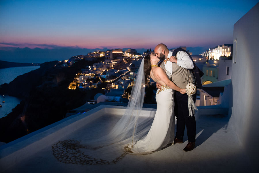 bride and groom kiss at night with landscape of oia, santorini in the background