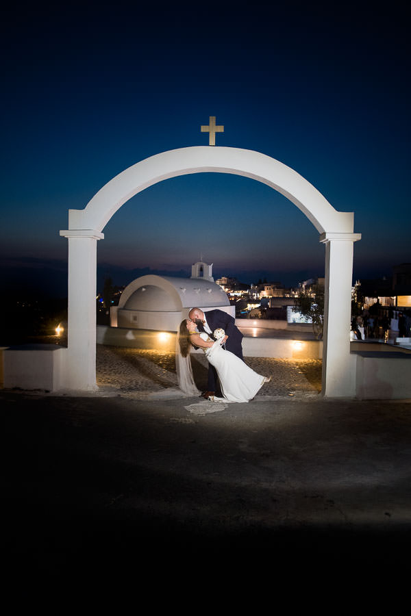 couple kiss under arch at destination wedding in santorini, greece at night