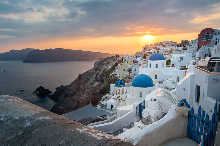 sunset view of Oia, Thira, Santorini, Greece with white houses and blue domes