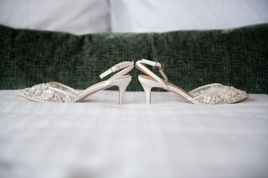 bella belle wedding shoes on bed for bride prep
