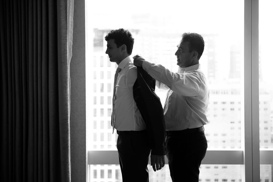 best man helps groom with his jacket before wedding at the mandarin oriental hotel in nyc
