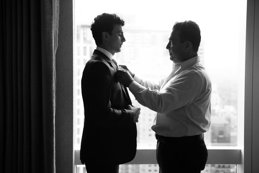 best man helps groom with his jacket before wedding